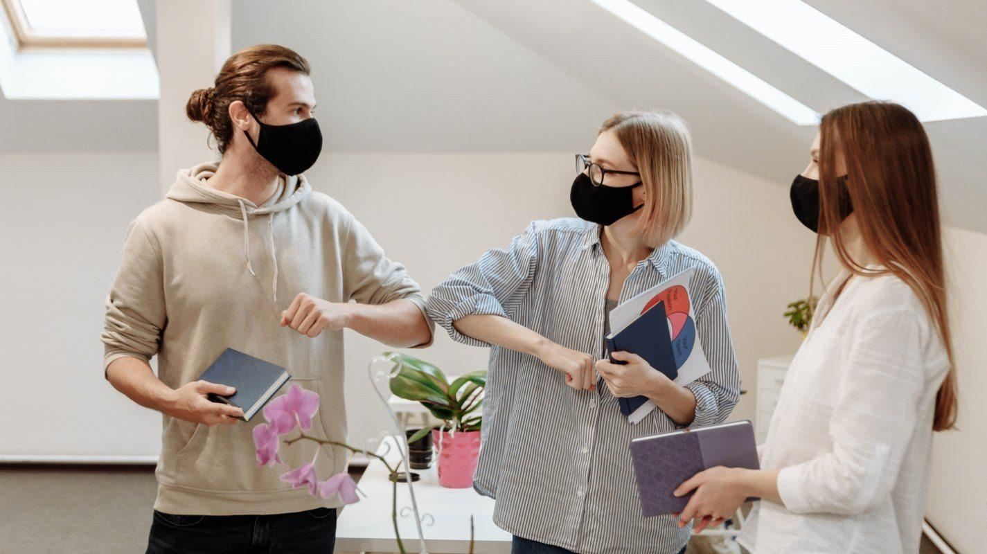 pandemic workplace elbow bump between colleagues